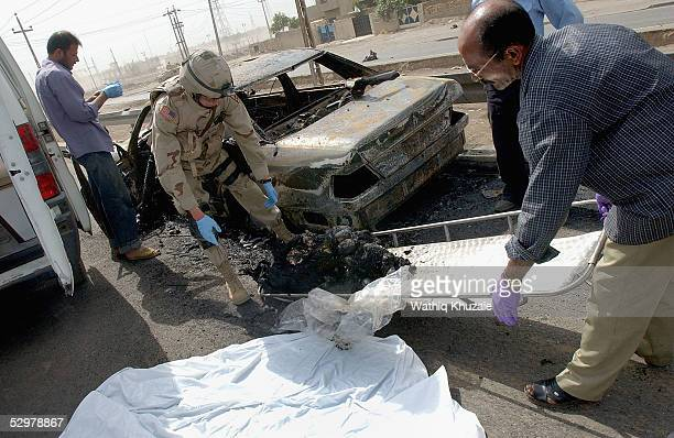 A US soldier helps an Iraqi paramedic carry a charred body at the scene of a suicide car bomb explosion which failed to hit a US military convoyMay...