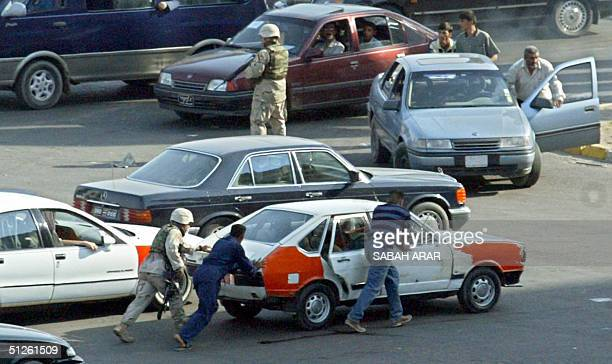 US soldier helps Iraqis to push a broken taxi at an intersection in central Baghdad 04 September 2004 US forces launched a major offensive in...