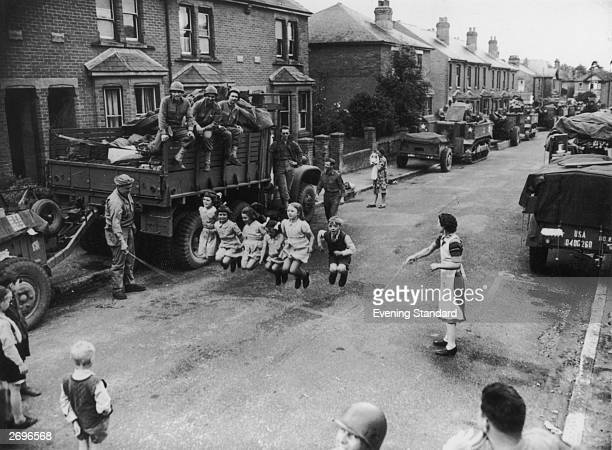US soldier helps some children with their skipping He is watched by his comrades in a town street in the south of England lined with equipment...
