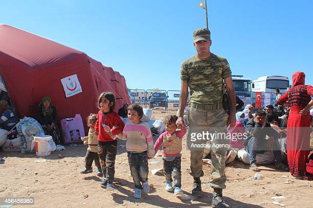 A soldier helps Syrian Kurdish children who fled from clashes between the Islamic State of Iraq and Levant militants and proKurdish Democratic Union...