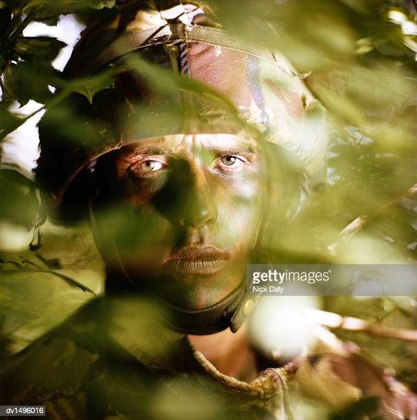 Soldier Hiding Behind Leaves Wearing a Camouflage Helmet