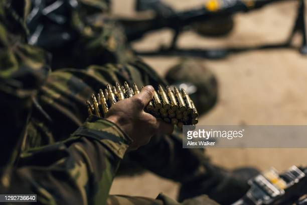 a soldier holding a belt of blank firing cartridges - gunman stock pictures, royalty-free photos & images