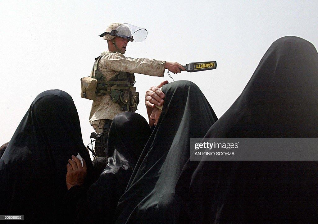 A US soldier, holding a metal detector, gestures as he controls the entrance of the Abu Ghraib prison, 20 May 2004 where Iraqi people are gathering in hope of getting information about their loved ones held by US forces at the detention center, 30 kms west of Baghdad. US troops faced further embarrassment amid claims they killed dozens of people at a wedding celebration in a remote western Iraqi town, at a time when the occupation forces are already reeling from a prison abuse scandal. AFP PHOTO/Antonio SCORZA