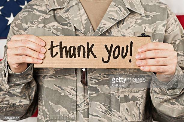 soldier holding a thank you sign to his chest - thank you military veterans stock photos and pictures