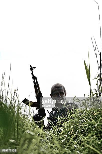 Soldier holding AK-47 crouching in bush
