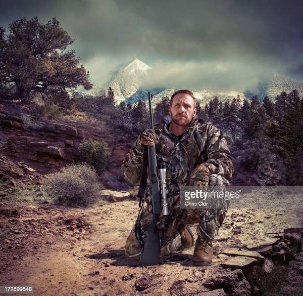 Soldier holding gun in dry rural landscape