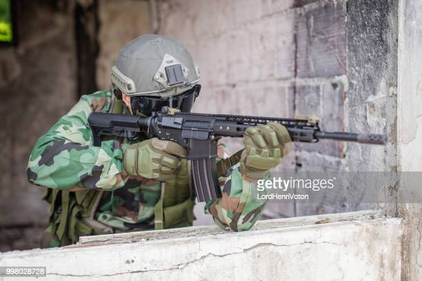 soldier holding machine gun. - covering stock pictures, royalty-free photos & images