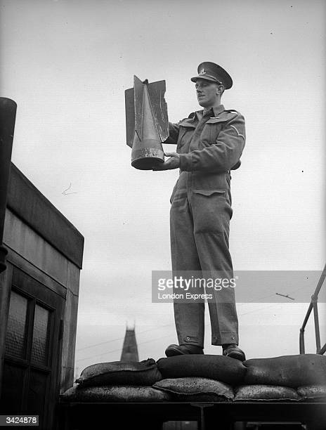 Soldier holding up the tailfin of a bomb.