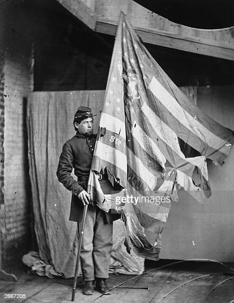 Soldier holding up the torn flag of the 8th Pennsylvania Reserve Colour Guard during the American Civil War.