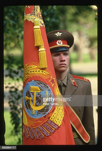 A soldier holds a flag bearing the Soviet coat of arms during a visit from President Mitterrand of France