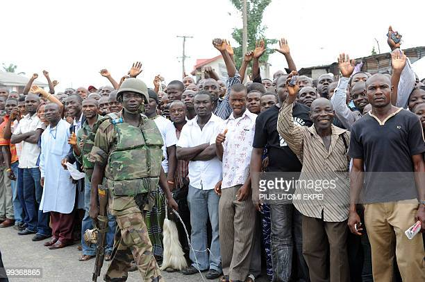 A soldier holds a horse whip to secure an area walks in front of supporters during a welcome cereomy of Nigerian President Goodluck Jonathan in Port...
