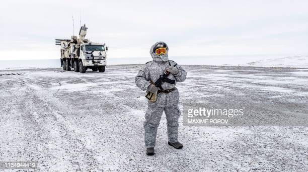 A soldier holds a machine gun as he patrols the Russian northern military base on Kotelny island beyond the Artic circle on April 3 2019 The Russian...