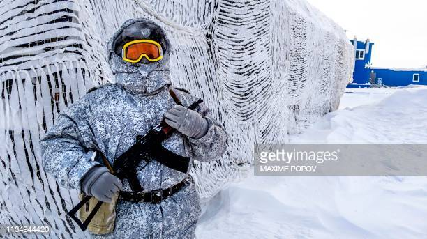 TOPSHOT A soldier holds a machine gun as he patrols the Russian northern military base on Kotelny island beyond the Artic circle on April 3 2019 The...