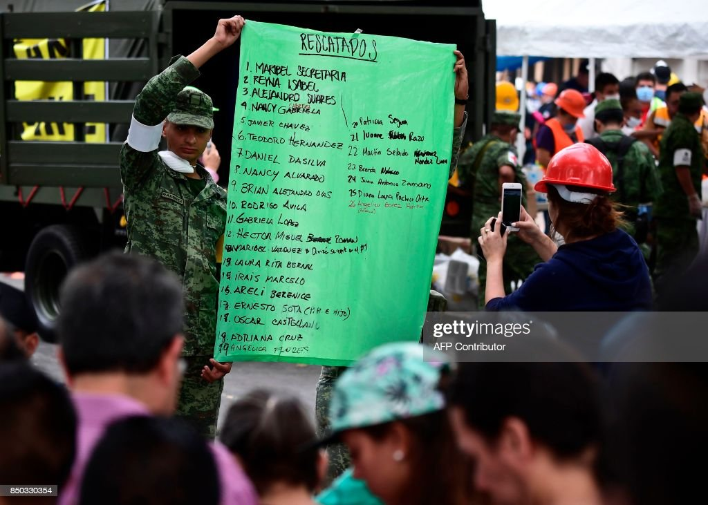 A soldier holds a placard with names of people rescued, in Mexico City, on September 20, 2017 one day after a powerful 7.1-magnitude quake devastated part of the country. At least 216 people were killed when a powerful 7.1-magnitude earthquake struck Mexico on Tuesday, including 21 children crushed beneath an elementary school that was reduced to rubble. /