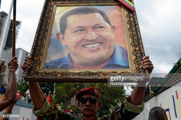 A soldier holds a portrait of late Venezuelan President Hugo Chavez during a rally to commemorate the 26th anniversary of former Chavez's 1992...
