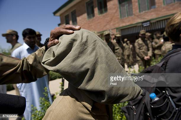 A soldier holds an alleged Taliban militant as he is presented to journalists inside an army base on May 22 2009 in Khwazakhela Pakistan Two days ago...