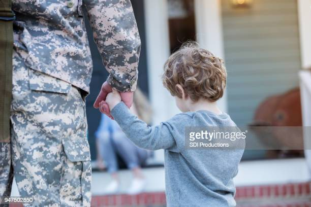 soldier holds hands with young son - military stock pictures, royalty-free photos & images