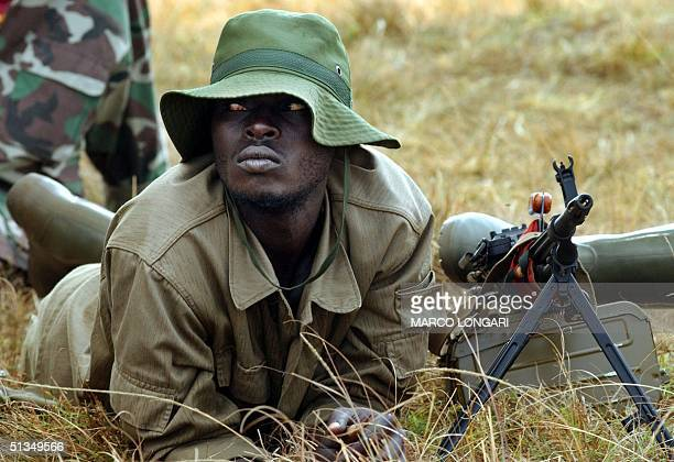 soldier holds position 16 July 2002 in the field of the Rwanda Patriotic Front airbase in the South Kivu Highlands Started last February 2002 the...