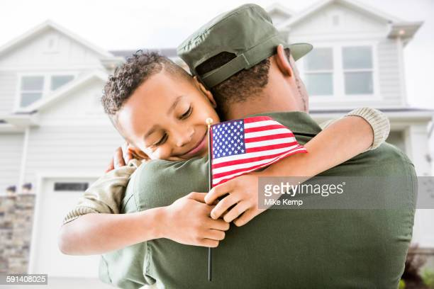 Soldier hugging patriotic son outside house