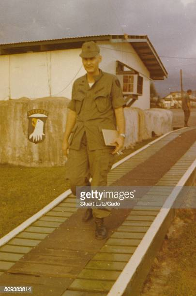 A soldier identified as Robert Swisher of the 101st Airborn Division can be seen walking down a wooden walkway exterior of a building with an air...
