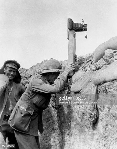 Soldier in a trench taking a photograph with a camera attached to a periscope