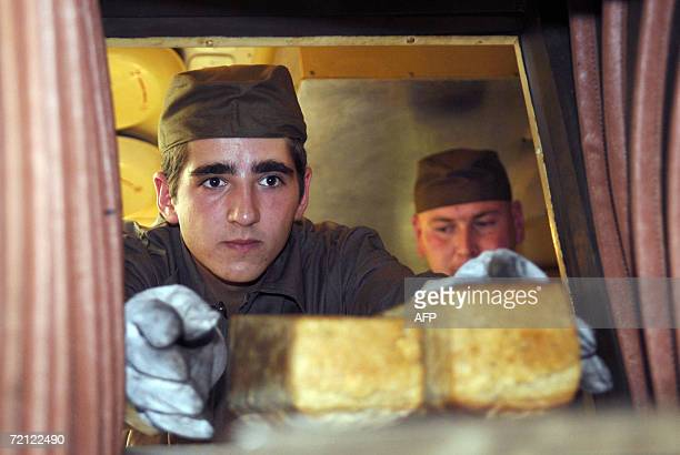 Soldier in an army kitchen removes bread from an oven during an exercise of the Slovakian multiple-function battalion from Hlohovec at a military...