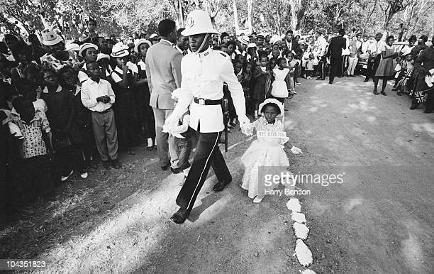 A soldier in ceremonial uniform leads a little girl in period costume by the hand during Queen Elizabeth II's royal tour of the Caribbean February...