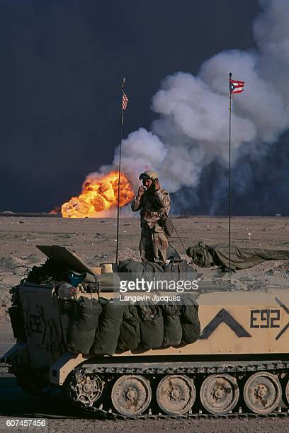 US soldier in front of burning oil wells along the road to Iraq
