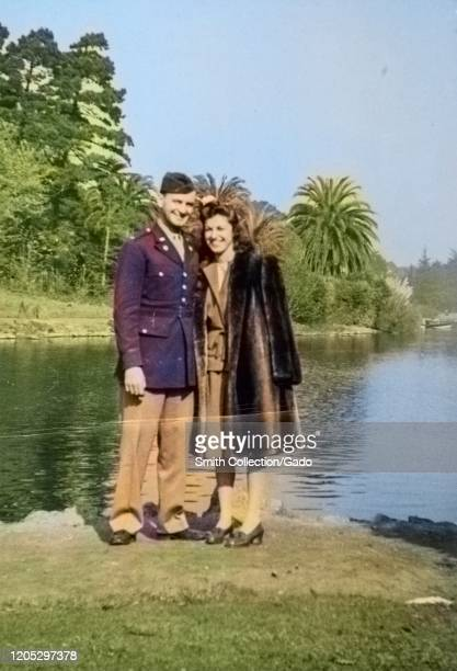 Soldier in military uniform stands with his arm around his wife, who wears a fur coat, and poses in front of the reflecting pool at the Palace of...