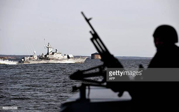 A soldier in silhouette on the corvette HMS Malmo watches sister ship corvette HMS Stockholm two of the three Swedish ships that will participate in...