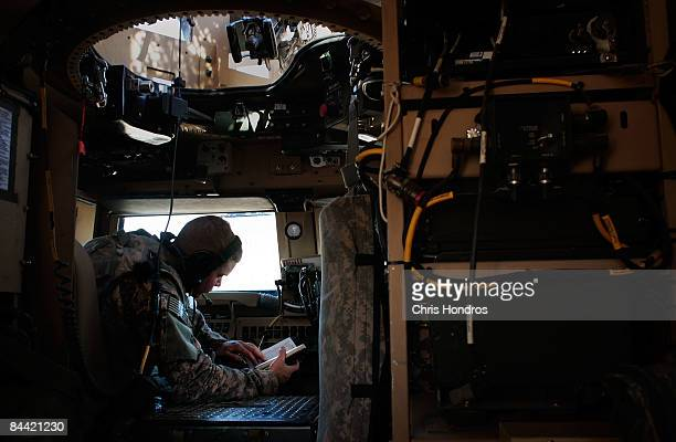 US soldier in the 1st Squad 10th Cavalry Regiment reads in the driver seat of an MRAP armored vehicle while waiting for his comrades to return from...