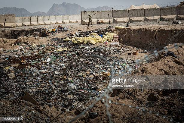 A soldier in the Afghan National Army walks past a burn pit at a command outpost recently handed over to the ANA from the United States Army on March...