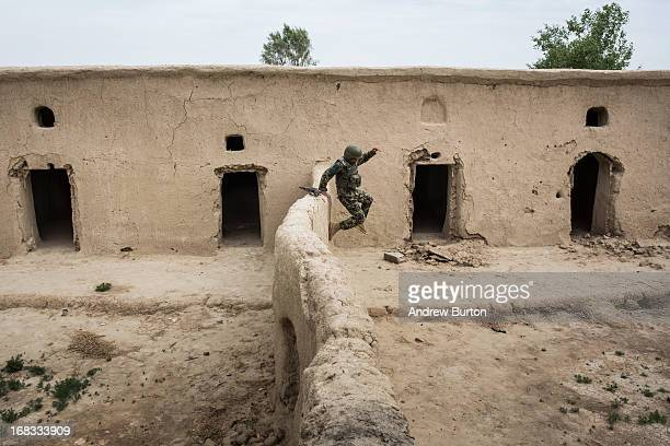 A soldier in the Afghan National Army's 6th Kandak 3rd company jumps down off of a wall during a joint patrol with the US Army's 1st Battalion 36th...