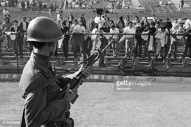 A soldier in the Chilean Army stands guard over political prisoners held at the National Stadium in Santiago On September 11 the Chilean Army...