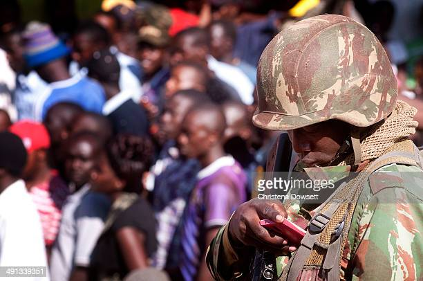 A soldier in the Kenya Defense Forces checks his phone after two improvised explosive devices went off in Gikomba market on May 16 2014 in Nairobi...