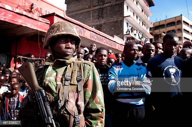 A soldier in the Kenya Defense Forces keeps control of onlookers after two improvised explosive devices went off in Gikomba market on May 16 2014 in...