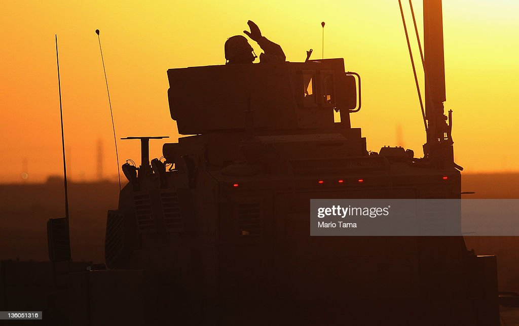 A soldier in the last American military convoy to depart Iraq, from the 3rd Brigade, 1st Cavalry Division, waves after crossing over the border into Kuwait on December 18, 2011 in Khabari Al Awazeem, Kuwait. Around 500 troops from the 3rd Brigade, 1st Cavalry Division ended their presence on Camp Adder, the last remaining American base, and departed in the final American military convoy out of Iraq, arriving into Kuwait in the early morning hours of December 18, 2011. All U.S. troops were scheduled to have departed Iraq by December 31st, 2011. At least 4,485 U.S. military personnel died in service in Iraq. According to the Iraq Body Count, more than 100,000 Iraqi civilians have died from war-related violence.