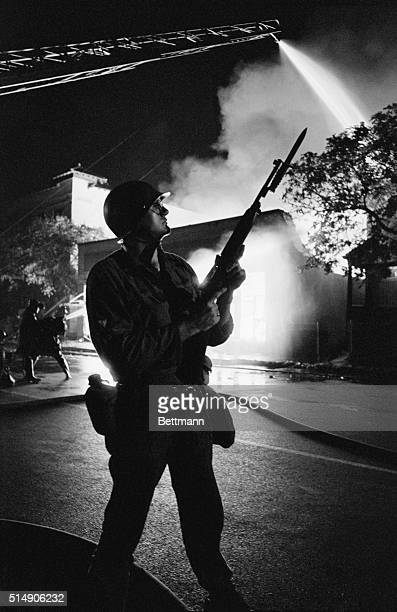 A soldier in the Michigan National Guard watches over Detroit firefighters trying to put out a blaze during the race riots of Detroit in July 1967