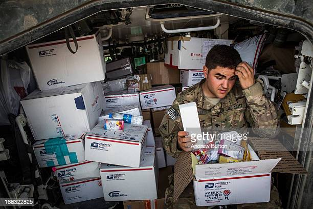 A soldier in the US Army's 1st Battalion 36th Infantry Regiment Charlie Company opens a gift package sent to him in the mail during a maintenance...