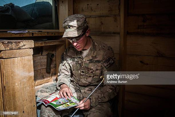 A soldier in the US Army's 1st Battalion 36th Infantry Regiment Charlie Company reads a comic book while pulling a security guard shift at Command...
