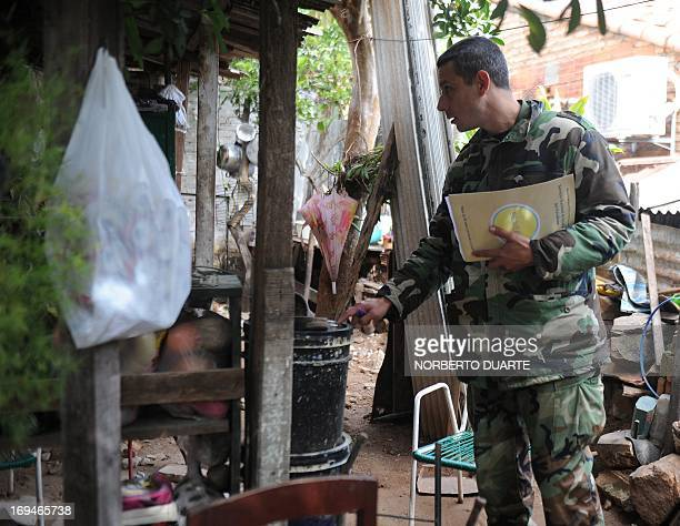 A soldier inspects a house in Asuncion during an operation to eradicate the Aedes aegypti mosquito vector of the dengue fever on May 25 2013 Dengue...