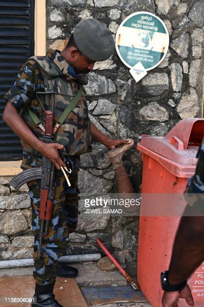 A soldier inspects a prosthetic limb left next to a garbage bin while patrolling an area near luxury hotels in Colombo on April 23 two days after a...