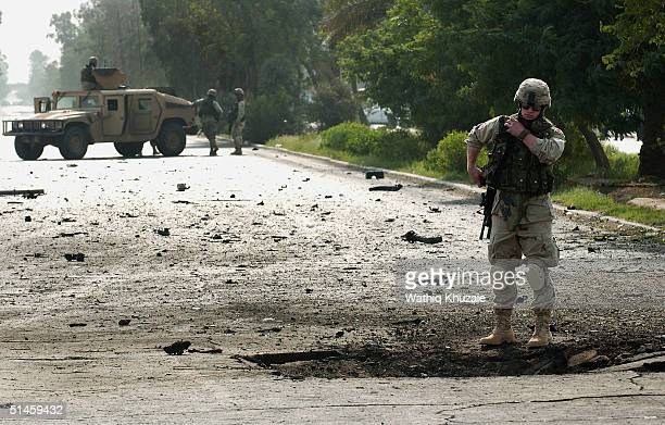 S soldier inspects the scene of a car bomb explosion near the oil ministry and police academy October 10 2004 in Baghdad Iraq Two car bombs exploded...