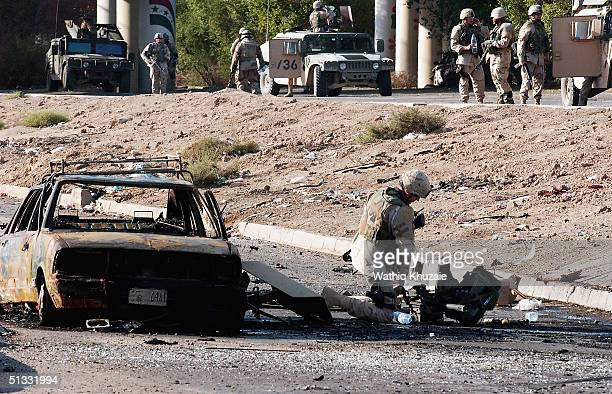 US soldier investigates at the scene of a car bomb explosion on September 21 2004 in Baghdad Iraq A car bomb exploded near a US military convoy...