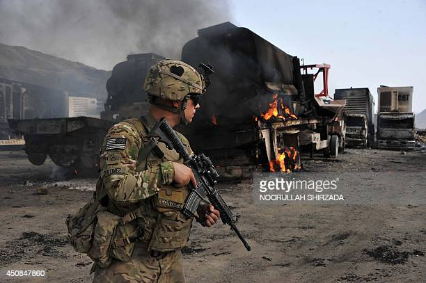 A US soldier investigates the scene of a suicide attack at the AfghanPakistan border crossing in Torkham Nangarhar province on June 19 2014 Three...