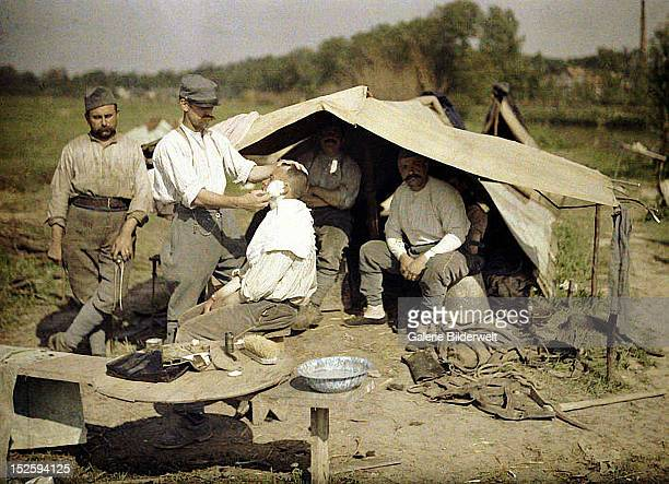 A soldier is being shaved by a barber in a French military encampment 1917 Color photo by Fernand Cuville Two other soldiers are waiting under a tent...