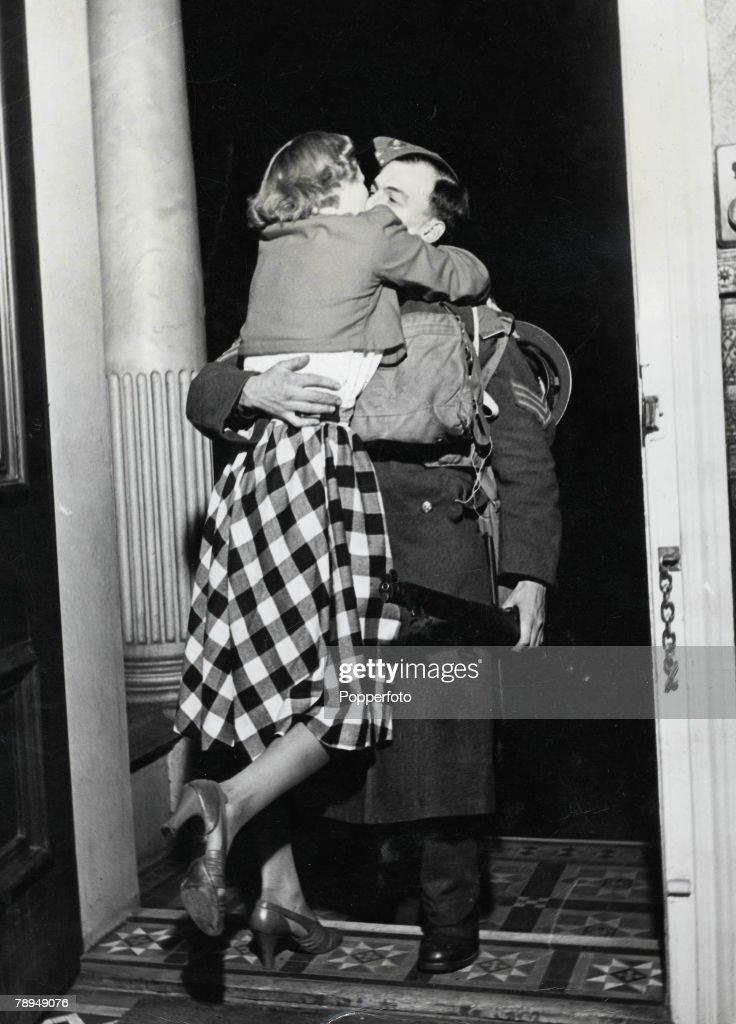 Volume 2. Page 128. Picture 9. World War Two. St. John's Wood, London, England. 1940+s. A soldier is greeted with a big hug and kiss from his ecstatic wife at the front door as he arrives home from France on leave for Christmas after serving his country i : News Photo