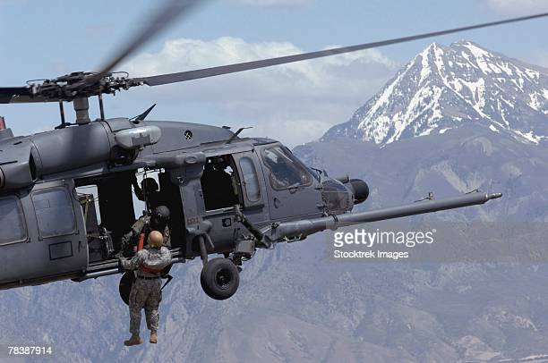 A soldier is lifted on board a HH-60 Pave Hawk.