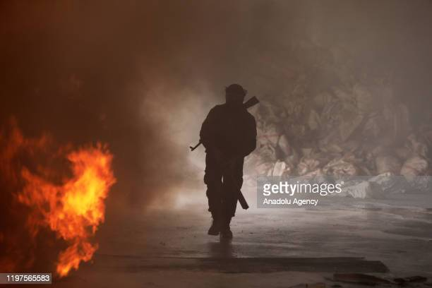 Soldier is seen as firefighters try to extinguish fire broke out after a bomb-laden vehicle exploded in Tal Abyad, Syria on January 30, 2020. 2...