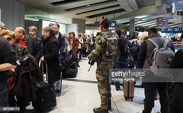 A soldier is seen as tourists wait in queues after they swarmed Charles De Gaulle airport in Paris France on November 14 2015 following the attacks...